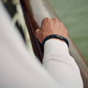 Navy blauwe armband met zwarte sluiting op leuning boot