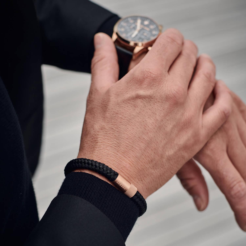 Zwarte armband met rosé gouden sluiting houdt horloge vast